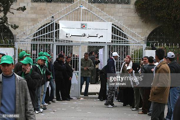Palestinians Hamas supporters stand opposite to Fatah supporters at the entrance to a polling station in the West Bank town of Hebron Wednesday...