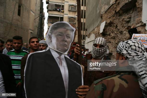 Palestinians hang an effigy bearing a poster of US President Donald Trump during a protest against Trump's decision to recognize Jerusalem as...