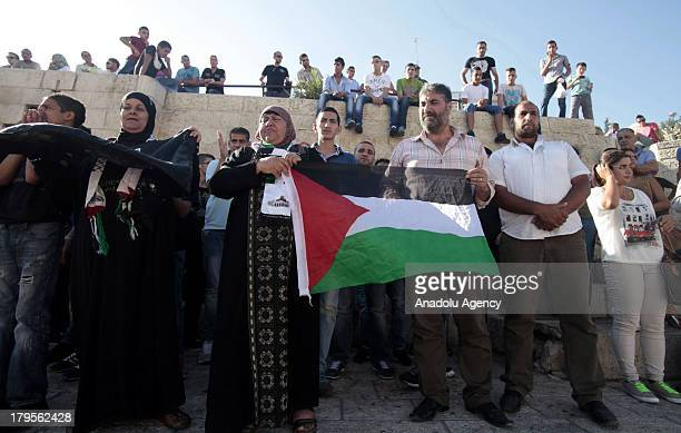 Palestinians hold a flag while demonstrating on 26 August 2013 in Jerusalem The demonstrators are protesting after Israel security forces raided...