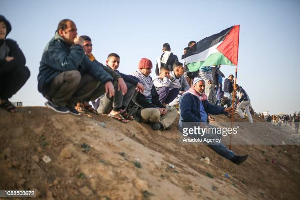 Palestinians hold a Palestinian flag during Israeli forces' intervention within Great March of Return demonstration near Al Bureij Refugee Camp of...