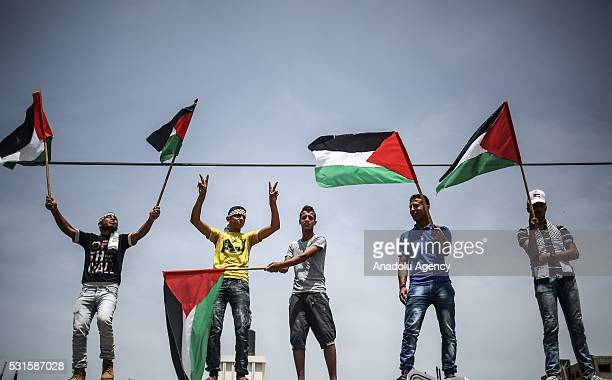 Palestinians hold a Palestinian flag during the 68th anniversary of Nakba also known as Day of the Catastrophe in Gaza City Gaza on May 15 2016