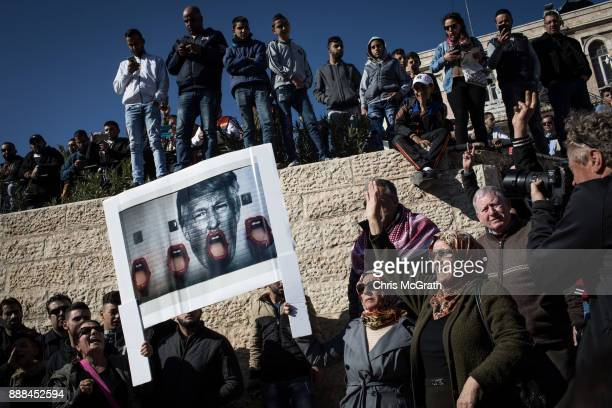 Palestinians hold a poster of President Trump as they protest outside the Damascus Gate of the Old City after Friday prayer on December 8 2017 in...