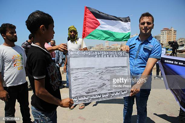Palestinians hold banner during a protest against the Israeli blocking of a boat of foreign activists from reaching Gaza at the seaport of Gaza city