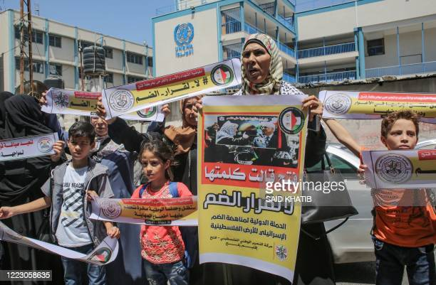 Palestinians hold banners as they take part in a protest against Israel's plans to annex parts of the occupied West Bank, in Rafah in the southern...