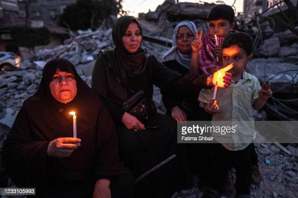 Palestinians hold candles during a rally amid the ruins of houses allegedly destroyed by Israeli strikes, in Beit Lahia Northern Gaza Strip on May...