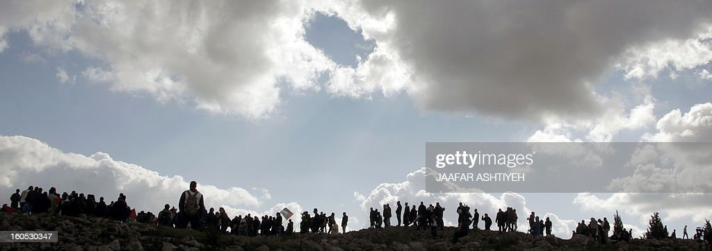 Palestinians hold flags on the top of a hill as they set up a new camp to protest against Jewish settlements near the West Bank village of Burin on February 2, 2013. An AFP correspondent said the Israeli army used tear gas and violence to remove hundreds of people who had set up four temporary huts and three tents near Burin, south of Nablus in the occupied West Bank, in a third attempt at the novel form of protest against Jewish settlements.