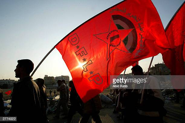 Palestinians hold national flags as they attend a demonstration against the Geneva Accord by different groups on December 1, 2003 in the Jabaliya...