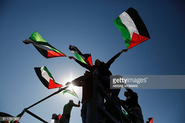 TOPSHOT Palestinians hold national flags during a march on February 19 2016 in the West Bank village of Bilin near Ramallah to mark the 11th...
