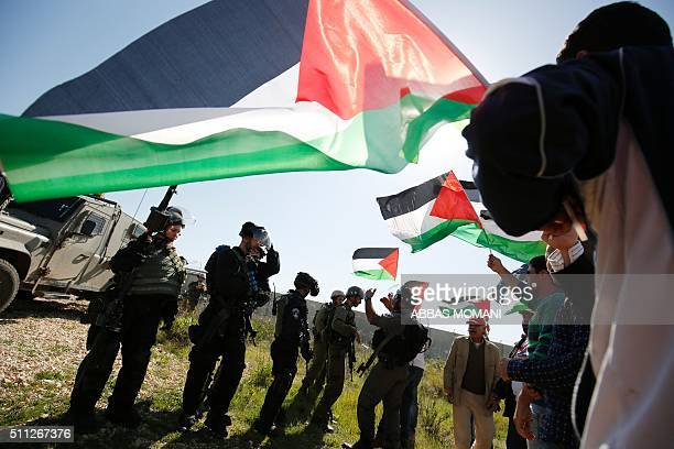 Palestinians hold national flags in front of Israeli security forces during clashes following a march on February 19 2016 in the West Bank village of...