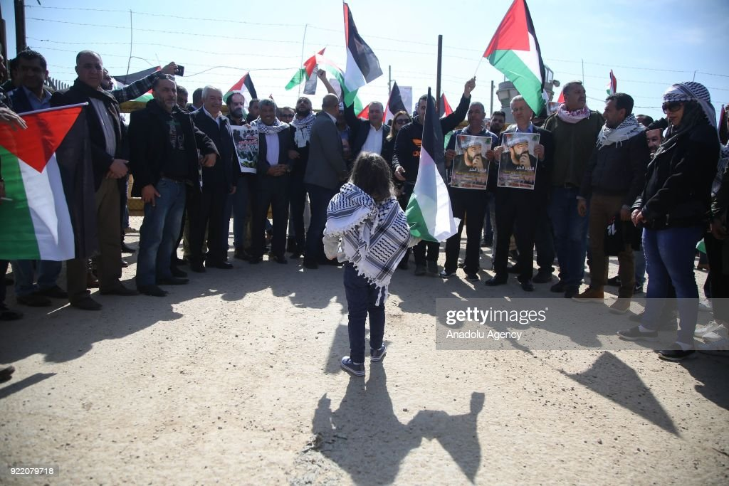Palestinians hold Palestinian flags during a protest, organized by Palestine Committee Against the Wall and Settlements, which has connection with Palestine Liberation Organization, against Munzir Amira's detention at Ofer Prison located in west of Ramallah, West Bank on February 21, 2018.