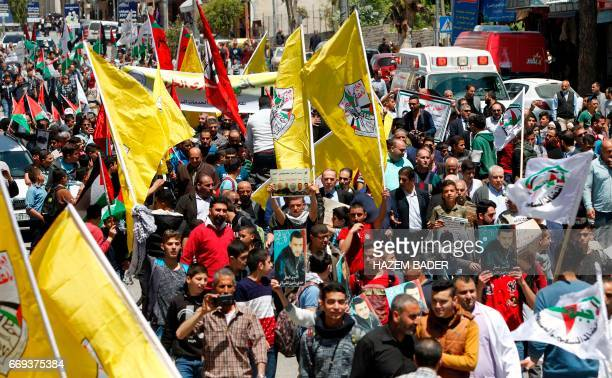 Palestinians hold pictures of prisoners and carry flags of the Fatah movement during a rally in the West Bank town of Hebron to show support to...