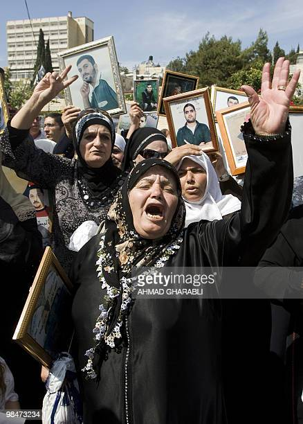Palestinians hold pictures of their relatives held in Israeli jails during a protest in east Jerusalem on April 15 2010 ahead of Prisoner Day The...