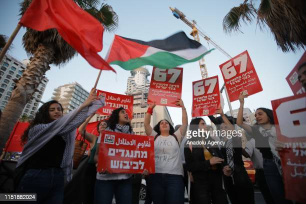 Palestinians hold placards and Palestinian flag as they gather to protest against Bahrain workshop and Deal of the Century plan in Tel Aviv Israel on...