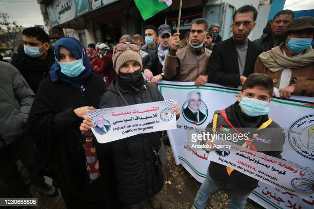 Palestinians hold placards as they gather during a protest against food aid cuts by the United Nations Relief and Works Agency , outside the UNRWA in...