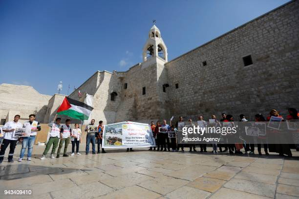 Palestinians hold placards in front of El Mehd Church during a protest after Israeli forces targeted Palestinian medical staff and journalists in...