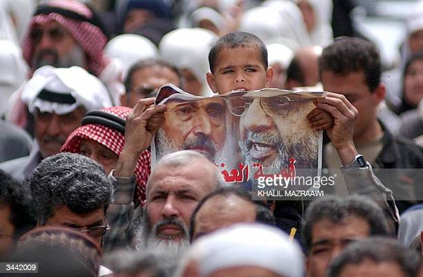 Palestinians hold portraits of late Hamas leaders Sheikh Ahmed Yassin and his successor Abdelaziz alRantisi during a demonstration at the Baqaa...