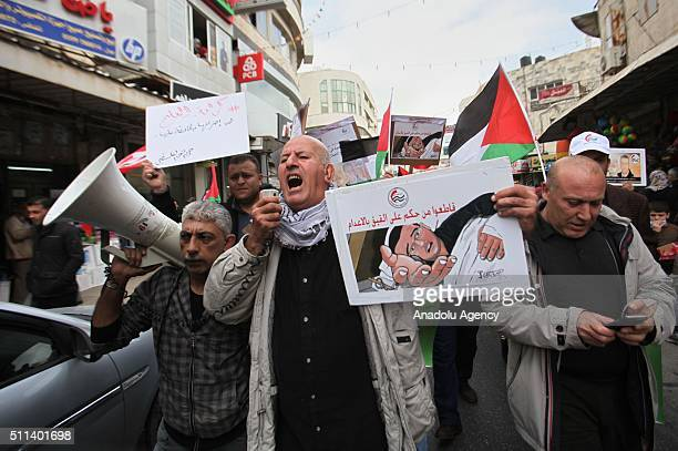 Palestinians hold poster of Palestinian journalist Mohammed elKayk who stages a hunger strike in an Israeli prison and chant slogans during a protest...