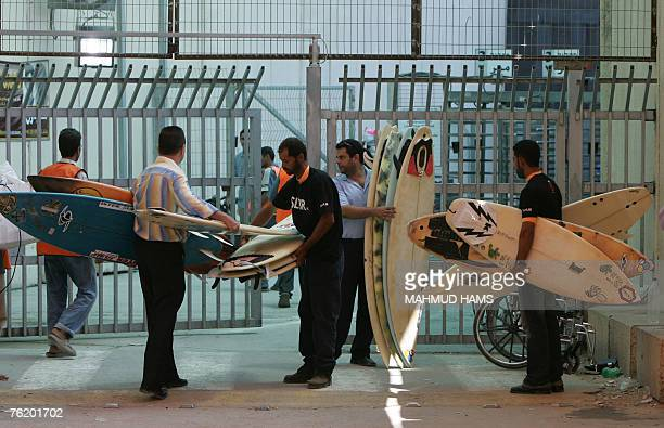 Palestinians hold surf boards as they are brought across from the Israeli side of the Erez crossing which separates Israel from the Gaza Strip 21...