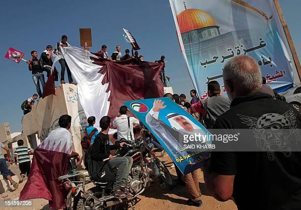 Palestinians hold the Qatari flag near the Rafah border crossing with Egypt prior to the arrival of Qatari Emir Sheikh Hamad bin Khalifa al-Thani to...