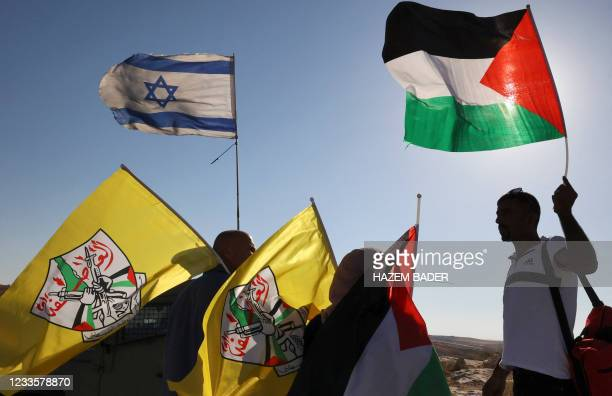 Palestinians hold their national and the Fatah flags as they stand near Israeli soldiers securing a march by Israeli settlers walking amidst...