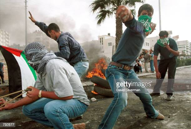 Palestinians hurl stones at Israeli troops during clashes October 16 2000 in the West Bank city of Ramallah US President Bill Clinton appealed to...