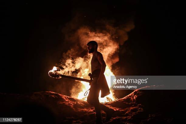 Palestinians ignite torches as they gather to stage a protest within Great March of Return demonstrations near Al Bureij Refugee Camp of Gaza City...