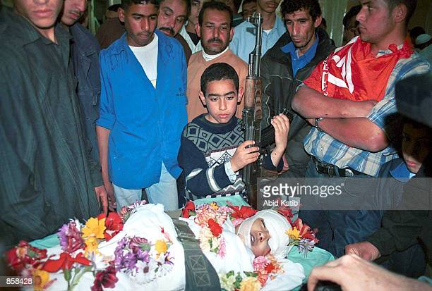 Palestinians including a boy with a gun look over the body of fouryearold Palestinian girl Reham Abu Taha who was hit by an Israeli bullet in her...