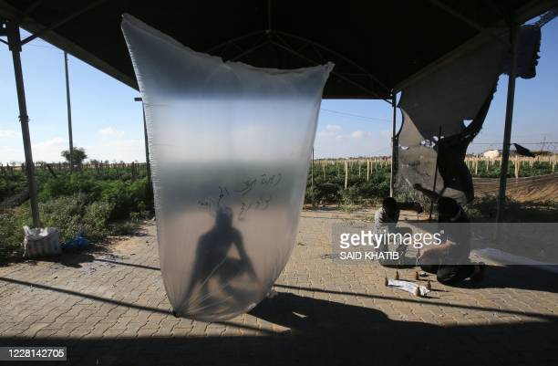 Palestinians inflate plastic bags before being attached with incendiary devices and flown towards Israel, near Rafah along the border between the...