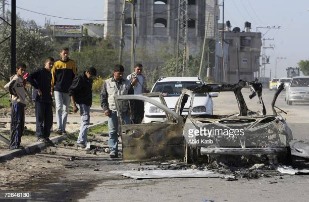 Palestinians inspect a car which was destroyed by an Israeli tank shell, November 26, 2006 in Jabalia, northern Gaza Strip. Palestinian militants in...