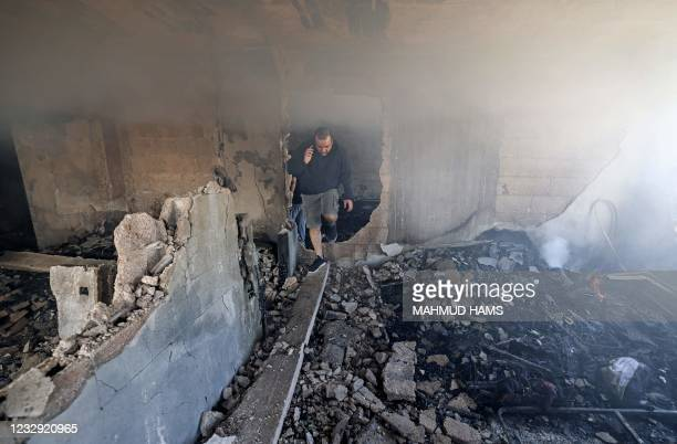 Palestinians inspect a damaged apartment of Al-Qahira Tower in Gaza City on May 16 following massive Israeli bombardment on the Hamas-controlled...