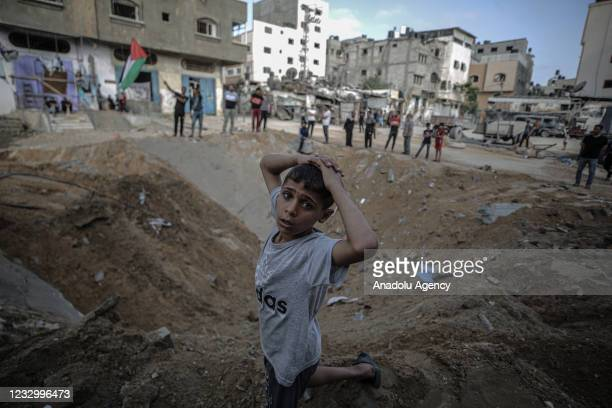 Palestinians inspect a hole after Israel's attack damaged streets in Gaza City, Gaza on May 20, 2021.