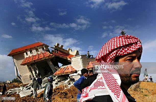 Palestinians inspect a house destroyed by Israeli bulldozers and tanks on January 3, 2008 at Khan Younis in the southern Gaza Strip. According to...