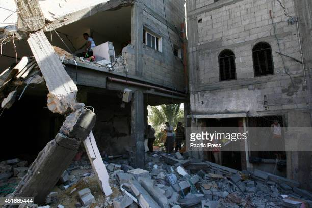 Palestinians inspect a house which police said was destroyed in an Israeli air strike in Khan Younis in the southern Gaza Strip. Israel officially...