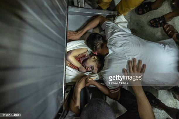 Palestinians inspect bodies of Palestinian children who were killed in an Israeli airstrike on May 16, 2021 in Gaza City, Gaza. More than 140 people...