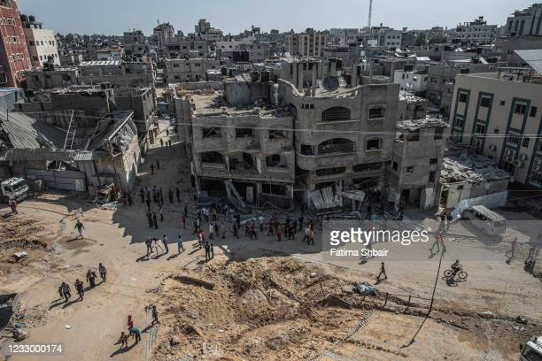 Palestinians inspect damage to buildings in Al-Saftawi street northern Gaza City on May 20, 2021 in Gaza City, Gaza. Civilian casualties continue to...