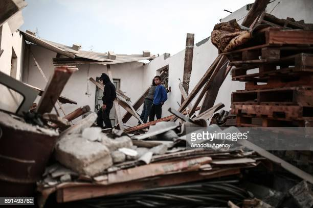 Palestinians inspect damaged buildings after an attack carried out by Israeli army on Tuesday evening in Khan Yunis Gaza on December 13 2017