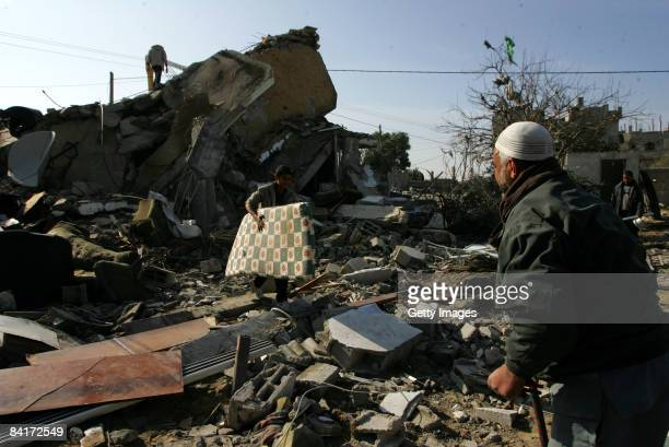 Palestinians inspect rubble after an Israeli airstrike on January 5 2009 in Rafah southern Gaza Israel is intensifying its widescale ground assault...