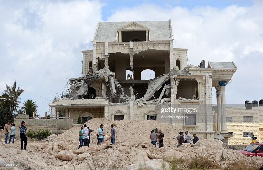 Palestinians inspect rubble of a house after it was demolished by Israeli bulldozers by reason of that the building near a separation barrier in Abu Dis town in of Jerusalem, Israel on September 29, 2014.