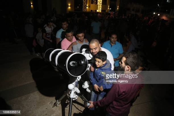 Palestinians inspect the Century's longest ''Blood Moon'' eclipse with a telescope in Ramallah West Bank on July 27 2018