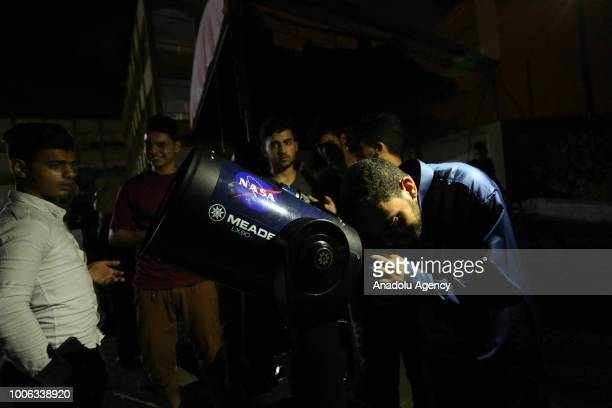 Palestinians inspect the Century's longest ''Blood Moon'' eclipse with a telescope in Khan Yunis Gaza on July 27 2018