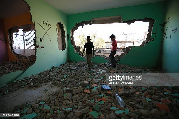 TOPSHOT Palestinians inspect the damage at the apartment of Hussein Abu Ghosh a Palestinian assailant who stabbed a woman to death in January after...