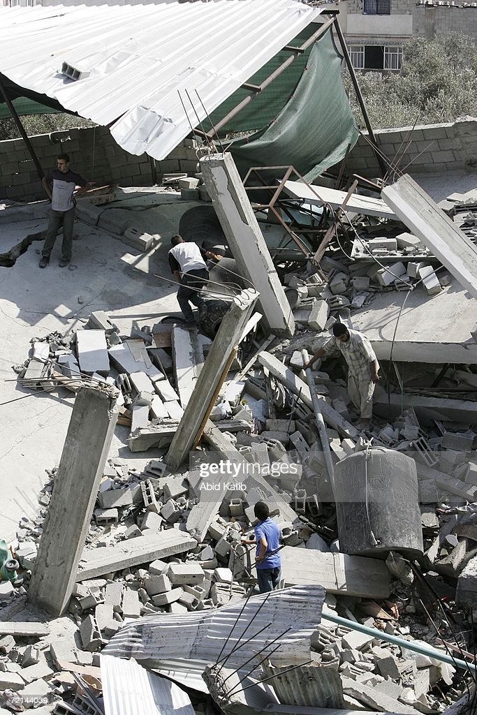 Palestinians inspect the damage to the house of Hamas lawmaker Mariam Farhat after it was destroyed by an Israeli missile October 11, 2006 in the Gaza Strip. The strike on the well-known female Palestinian lawmaker has reportedly been characterized as an attack on a weapons storage and manufacturing facility by an Israeli spokesperson.