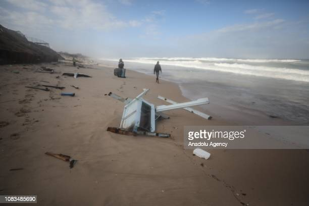 Palestinians inspect the parts of the Egyptian fishermen's boat which was destroyed by unusually rough seas in Deir al Balah Gaza on January 17 2019...