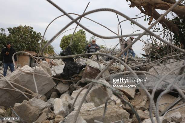Palestinians inspect the remains of a house after Israeli soldiers destroyed three houses of Palestinians in Jenin West Bank on January 18 2018