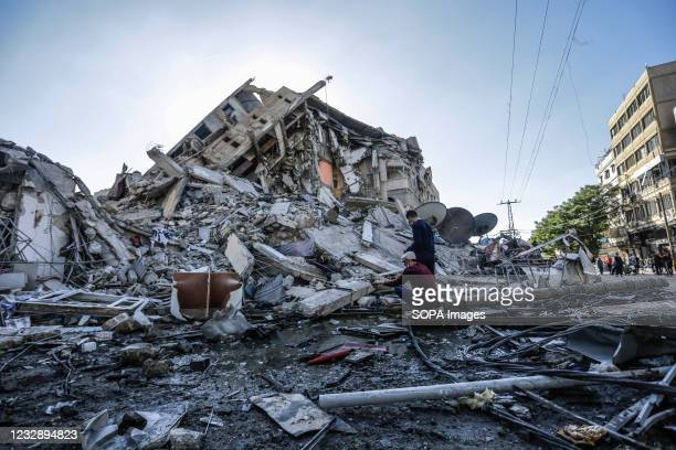 Palestinians inspect the rubble of the destroyed Al-Shorouq tower after an Israeli strike in Gaza City. In response to days of violent confrontations...