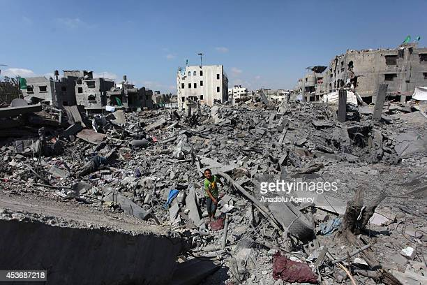 Palestinians inspect the rubble of their destroyed houses and collect usable stuff in Shujaya neighborhood Gaza on August 16 2014 Palestinians do not...