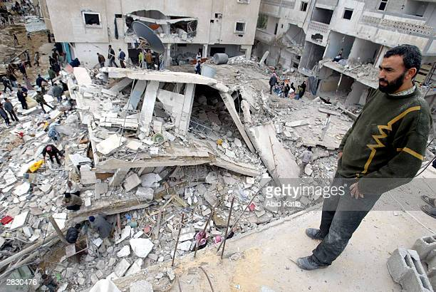 Palestinians inspect the rubble of their destroyed houses on December 24 2003 in Rafah refugee camp in the southern Gaza Strip Israeli troops and...