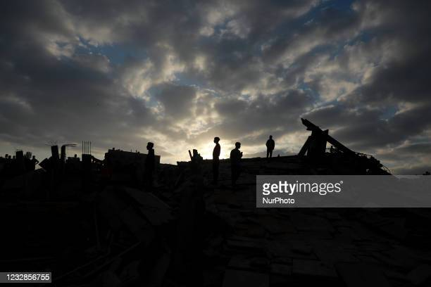 Palestinians inspect the ruins of buildings which were destroyed in Israeli air strikes amid a flare-up of Israeli-Palestinian violence, in the...