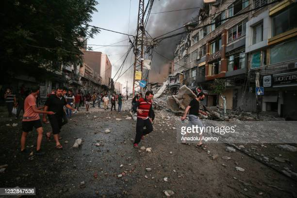 """Palestinians inspect the site after Israeli airstrikes hit and collapsed a 14-story Palestinian building called """"Ash-Shuruq"""" at Omar Al-Mukhtar..."""