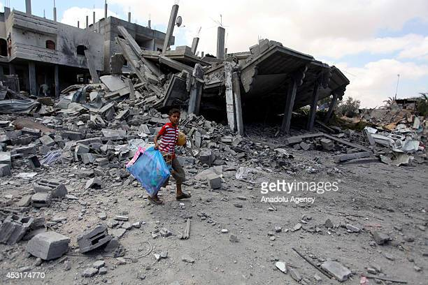 Palestinians inspect the wreckages of buildings after Israeli assaults in Rafah Gaza on August 4 2014 The latest fatalities bring to 1867 the number...